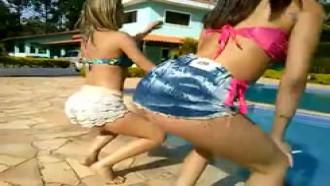 Duas gostosas dançando na beira da piscina