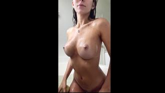 Modelo nua no banho lavando os peitinhos